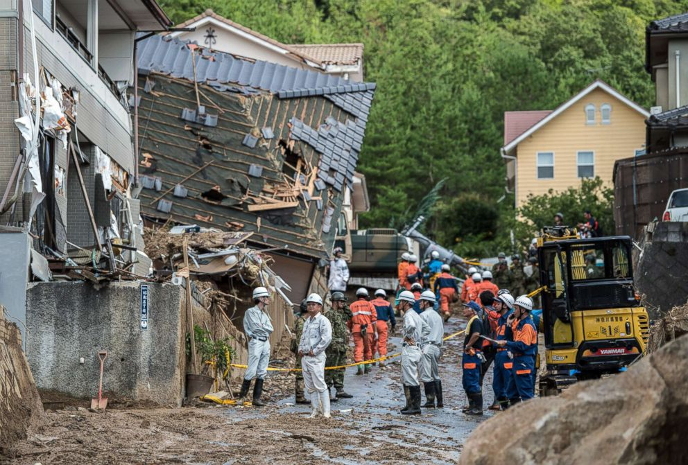 PHOTO: Emergency services members work next to houses destroyed by a landslide on July 8, 2018 in Kumano near Hiroshima, Japan.
