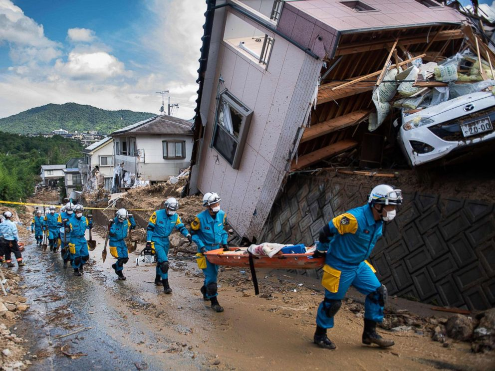 PHOTO: Police arrive to clear debris scattered on a street in a flood hit area in Kumano, Hiroshima prefecture on July 9, 2018.