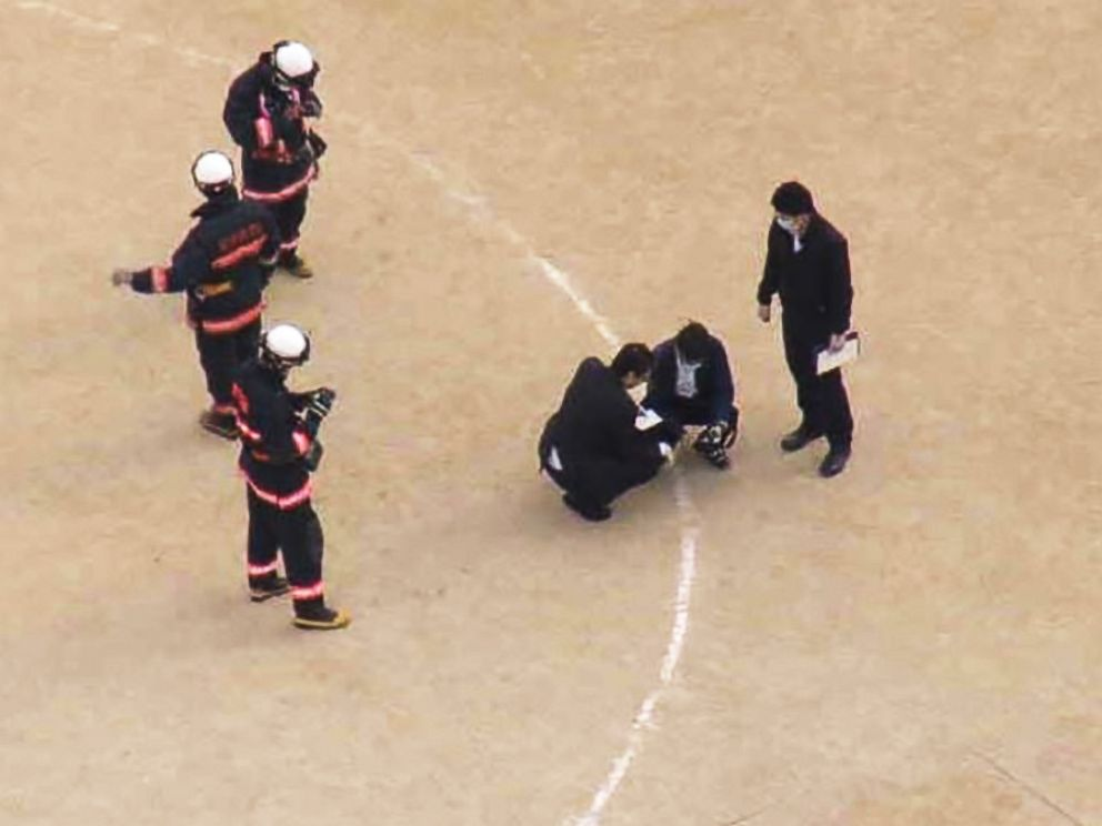 PHOTO: Investigators examine the site where the window landed on the schools sports field.