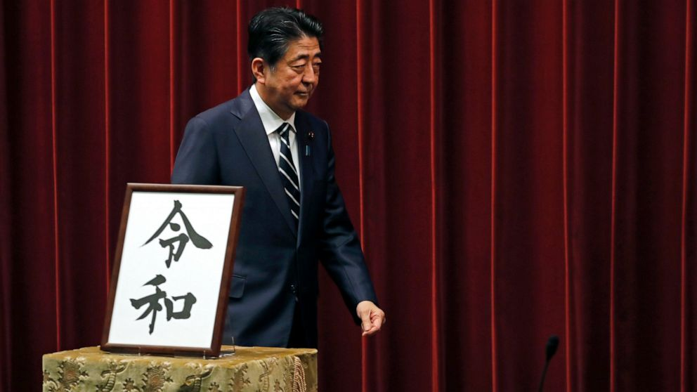"Japanese Prime Minister Shinzo Abe walks past the name of new era ""Reiwa"" on display at the Prime Minister's office in Tokyo, Monday, April 1, 2019."
