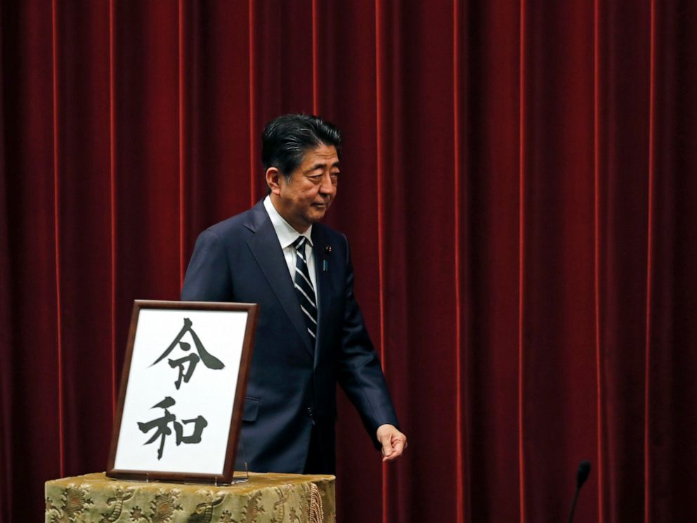 PHOTO: Japanese Prime Minister Shinzo Abe walks past the name of new era Reiwa on display at the Prime Ministers office in Tokyo, Monday, April 1, 2019.