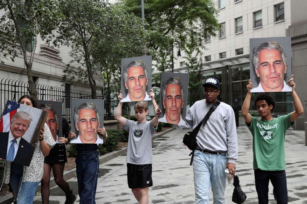 PHOTO: Demonstrators hold signs protesting Jeffrey Epstein, as he awaits arraignment in New York, July 8, 2019.