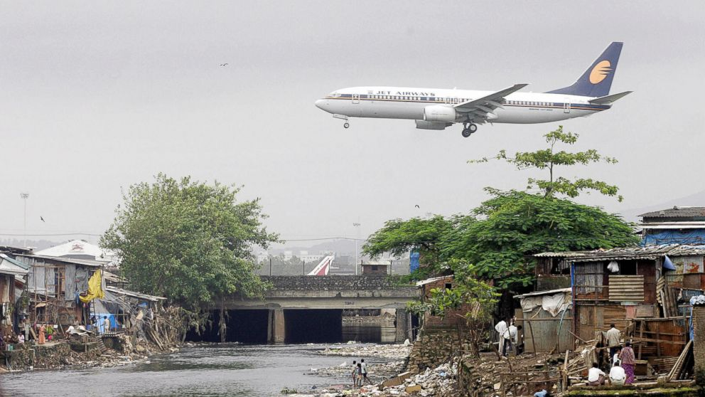 A Jet Airways plane flies over the Mithi River on its way to landing at Mumbai airport, at Bharat Nagar in Hyderabad, India,  in this Aug. 16, 2005 file photo.