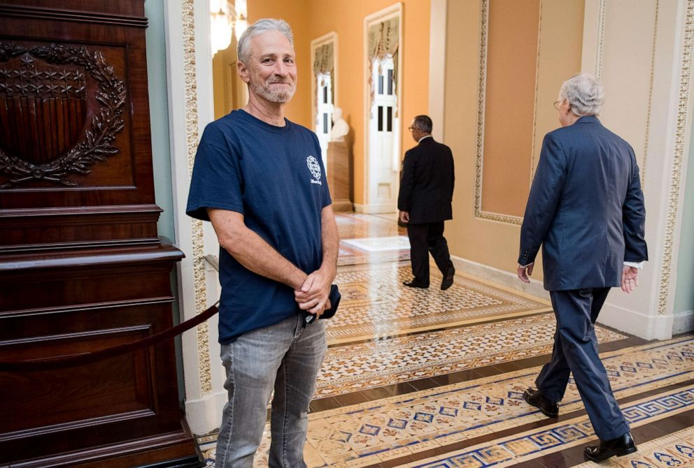 PHOTO: Jon Stewart, former host of The Daily Show, smiles as Senate Majority Leader Mitch McConnell walks by at the Ohio Clock Corridor in the Capitol, July 23, 2019.