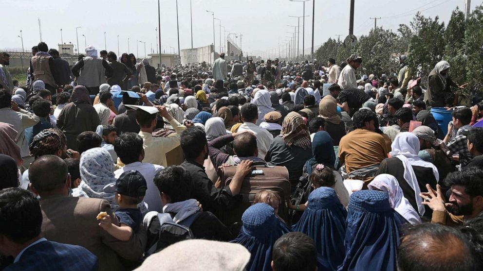 PHOTO: Afghans gather on a roadside near the military part of the airport in Kabul, Aug. 20, 2021, hoping to flee from the country after the Taliban's military takeover of Afghanistan.