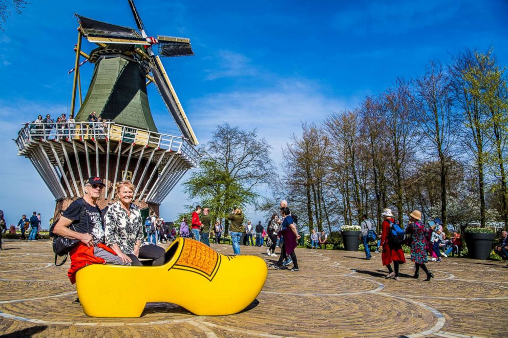 PHOTO: Visitors sit in a wooden shoe behind a windmill at the Keukenhof gardens, April 17, 2018, in Lisse, The Netherlands.
