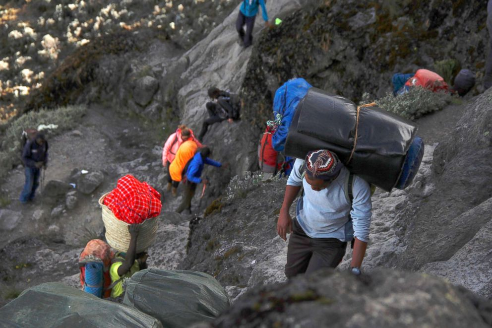 The group being led by porters as they hike up Barranco Wall, a steep climb on Mount Kilimanjaro.
