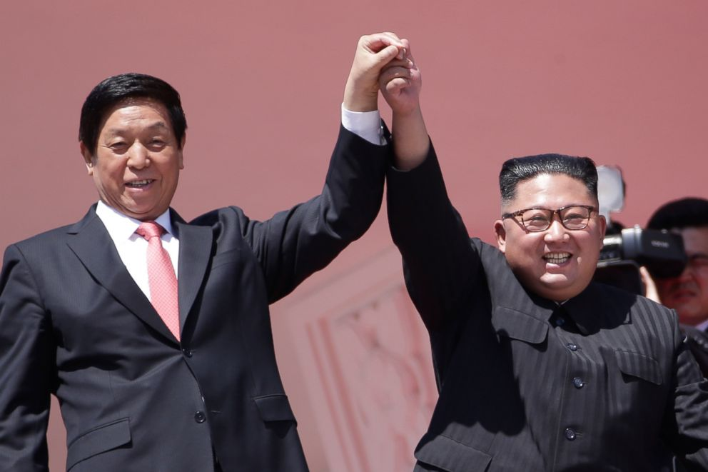 PHOTO: North Korean leader Kim Jong Un, right, raises hands with Chinas third highest ranking official, Li Zhanshu, during a parade for the 70th anniversary of North Koreas founding day in Pyongyang, North Korea, Sept. 9, 2018.