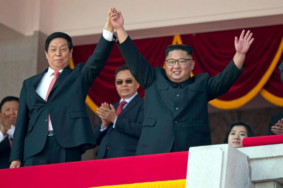 PHOTO: North Korean leader Kim Jong Un raises hands with Chinas third highest ranking official, Li Zhanshu, during a parade for the 70th anniversary of North Koreas founding day in Pyongyang, North Korea, Sept. 9, 2018.