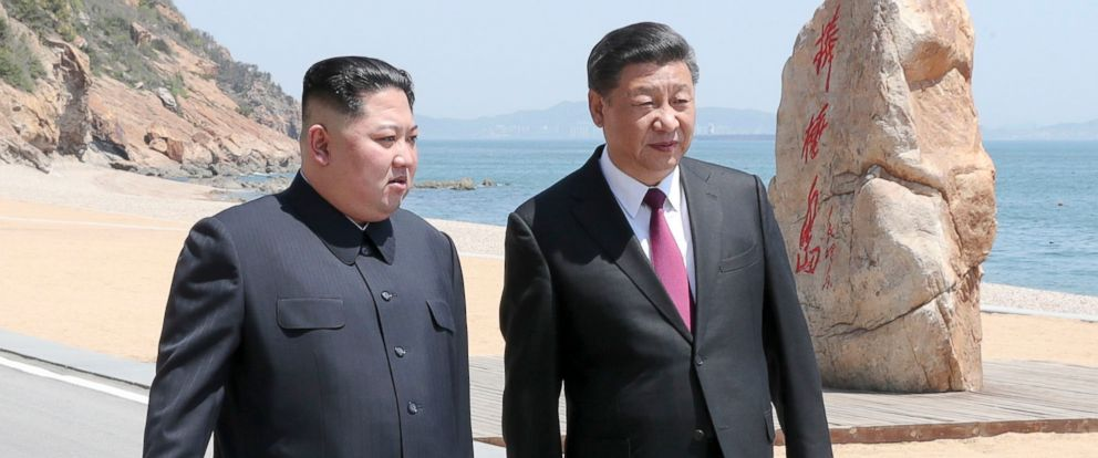 PHOTO: North Korean leader Kim Jong Un and Chinese President Xi Jinping walk during a meeting in Dalian in northeastern Chinas Liaoning Province.