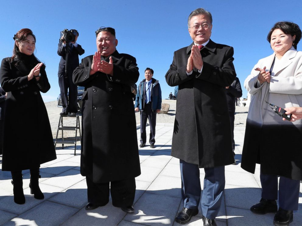 South Korean President Moon Jae-in, second from right, his wife Kim Jung-sook, right, North Korean leader Kim Jong Un, second from left, and his wife Ri Sol Ju clap hands on the Mount Paektu in North Korea on Thursday.