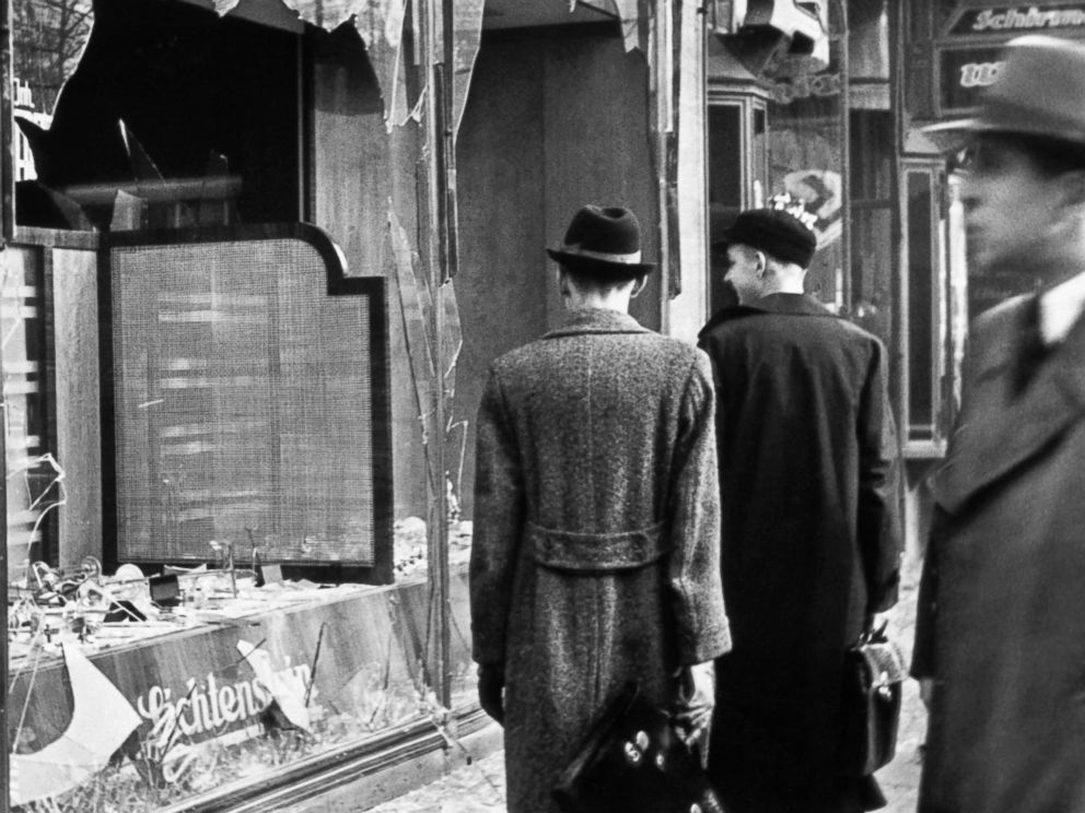 PHOTO: Pedestrians look at the broken windows of a Jewish-owned shop targeted by Nazis on the evening of Kristallnacht in Germany, 1938.