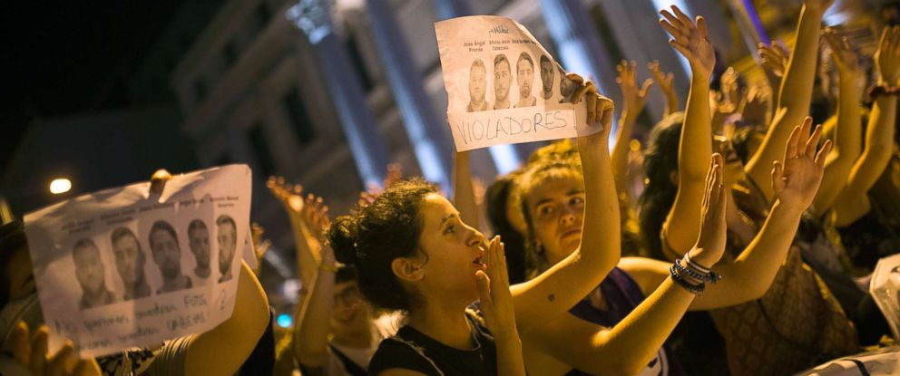 "PHOTO: Women, some holding photographs of the five men known as ""La Manada"" or ""The Pack"" and reading: ""Rapists"", shout slogans outside the Spanish parliament during a protest in Madrid, April 26, 2018."
