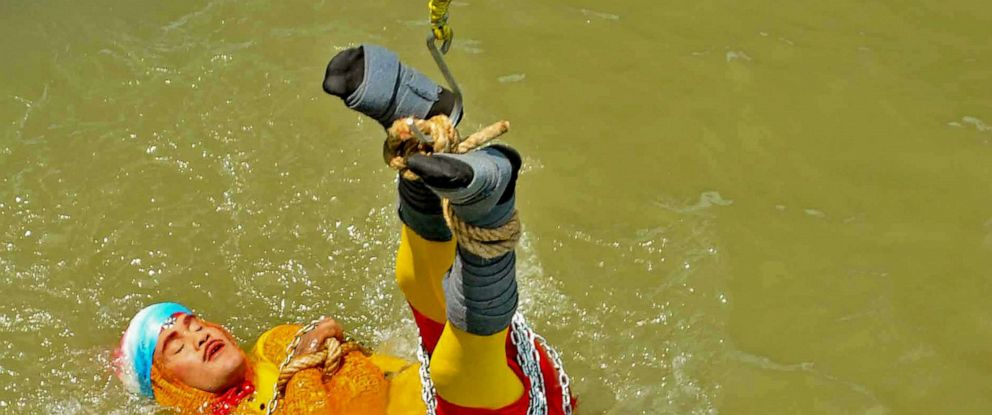 "PHOTO:Indian stuntman Chanchal Lahiri, known by his stage name ""Jadugar Mandrake"", is lowered into the Ganges river, while tied up with steel chains and ropes, in Kolkata, June 16, 2019."