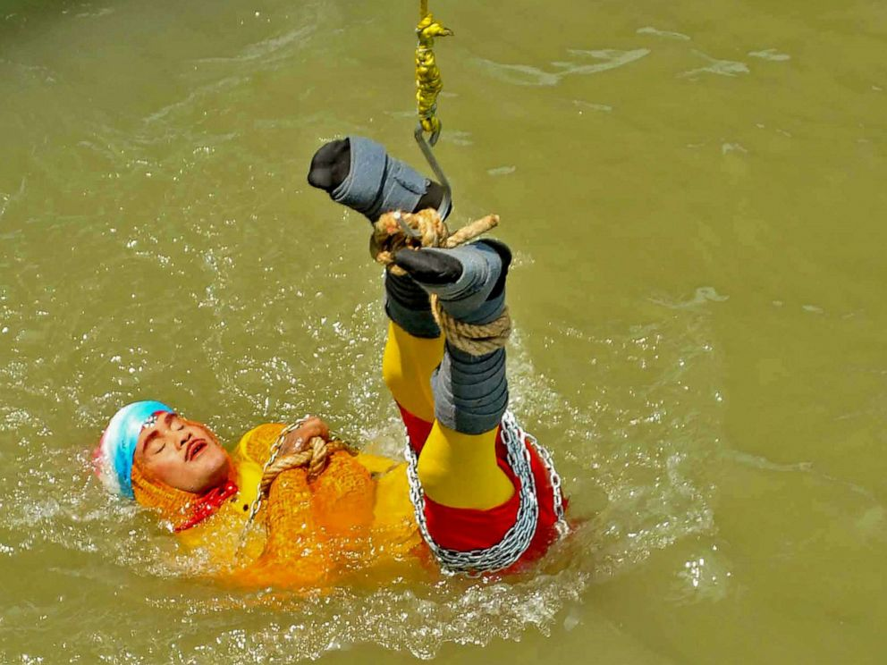 PHOTO:Indian stuntman Chanchal Lahiri, known by his stage name Jadugar Mandrake, is lowered into the Ganges river, while tied up with steel chains and ropes, in Kolkata, June 16, 2019.