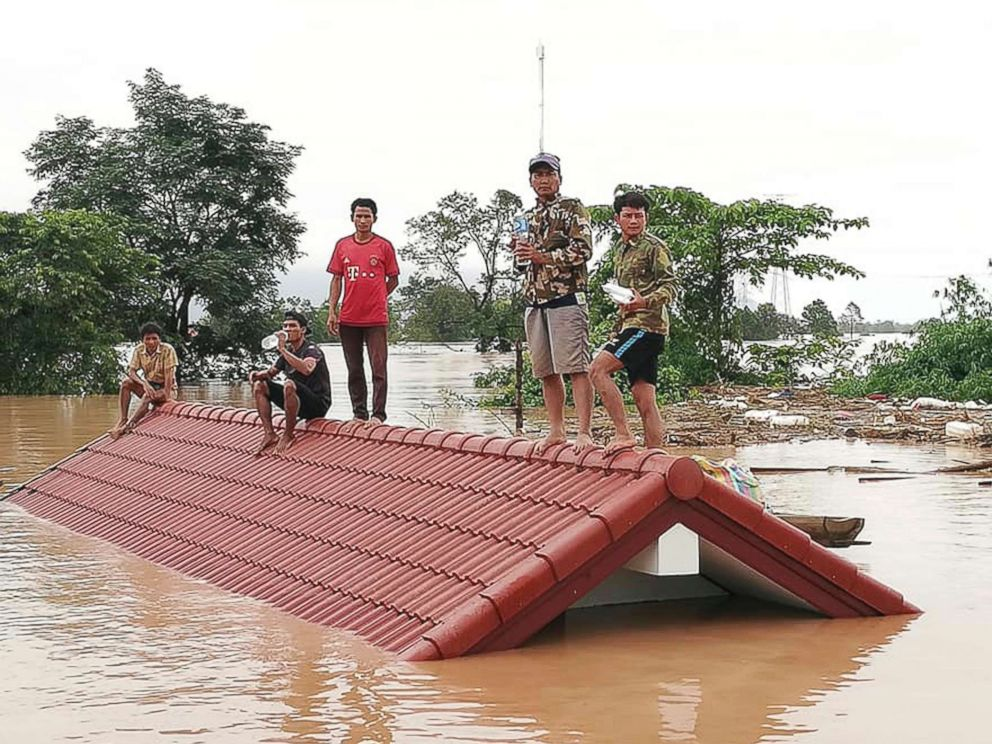 PHOTO: Villagers take refuge on a rooftop above flood waters from a collapsed dam in the Attapeu district of southeastern Laos, July 24, 2018.