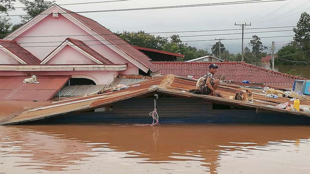 A villager takes refuge on a rooftop above flood waters from a collapsed dam in the Attapeu district of southeastern Laos, July 24, 2018. The official Lao news agency KPL reported Tuesday that the Xepian-Xe Nam Noy hydropower dam in Attapeu province collapsed Monday evening, releasing large amounts of water that swept away houses and made more than 6,600 people homeless.