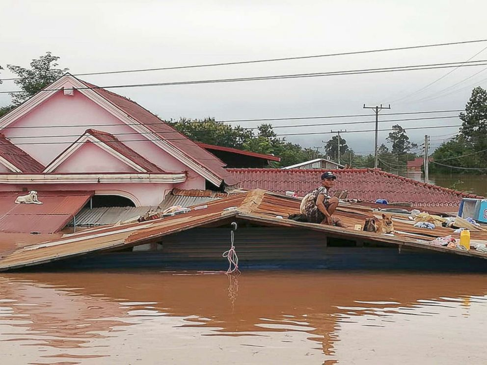 PHOTO: A villager takes refuge on a rooftop above flood waters from a collapsed dam in the Attapeu district of southeastern Laos, July 24, 2018.