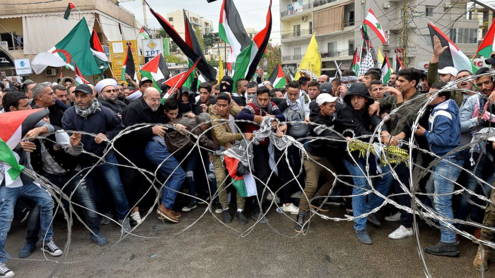 Protesters try to remove barbed wires that block a road near the U.S. embassy during a protest against President Donald Trump's decision to recognize Jerusalem as the Capital of Israel, in Awkar, east of Beirut, Lebanon, Dec. 10, 2017.