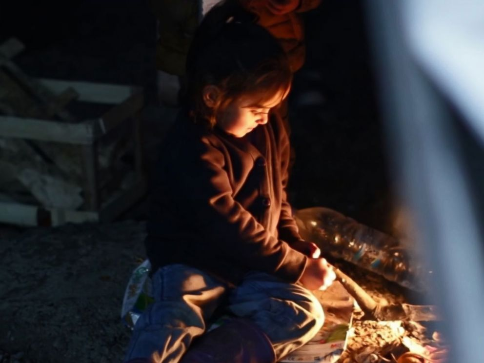 PHOTO: In Lesbos Moria refugee camp, children gather around fires to keep warm.