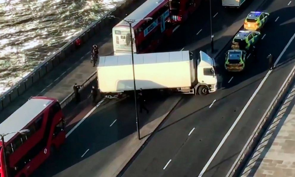 PHOTO: In this image made from video provided by Luke Poulton, armed police surround a truck parked across lanes of traffic on London Bridge, following an incident in central London, Nov. 29, 2019.