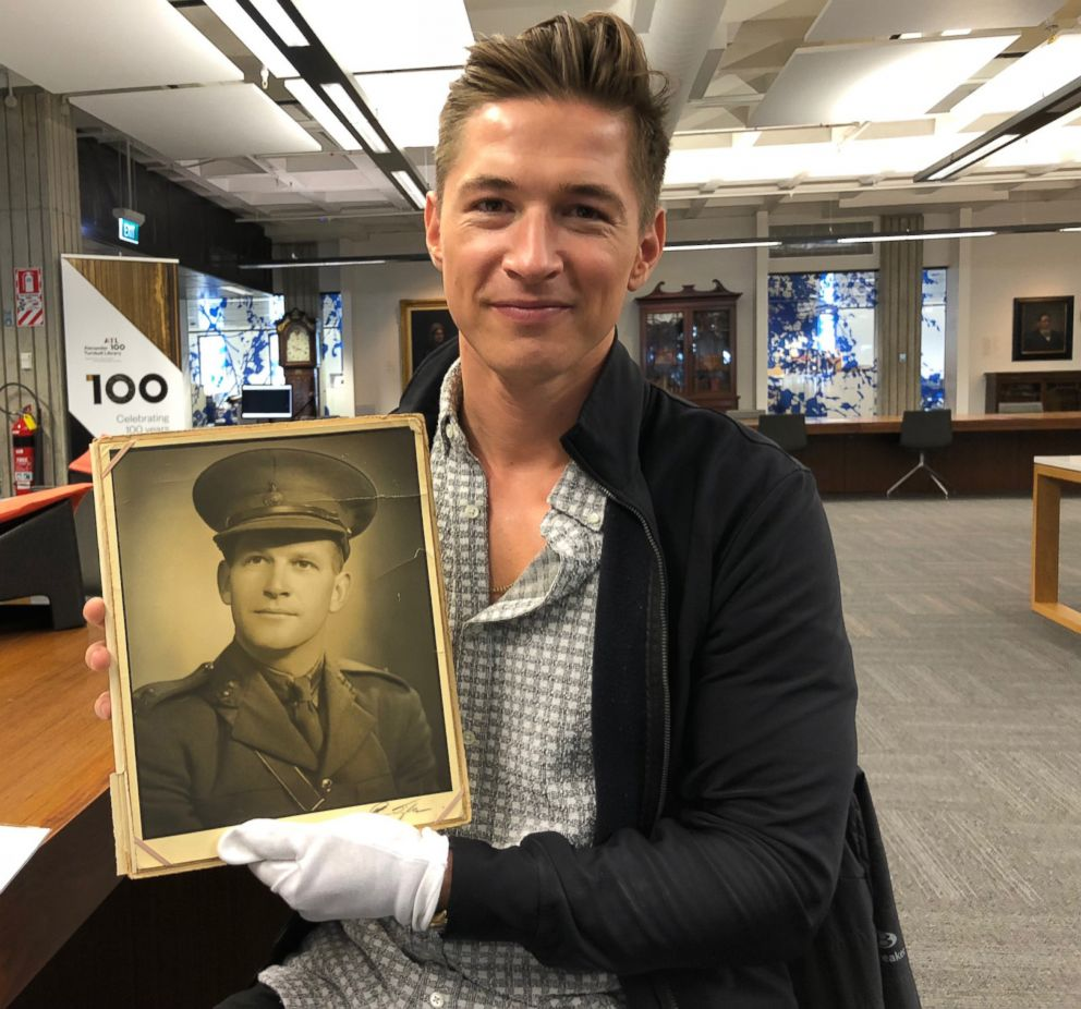 PHOTO: James Longman holding a photo of his grandfathers photo.