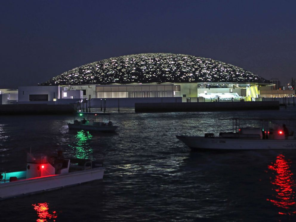 PHOTO: Boat lights are reflected on the water in front of the Louvre Abu Dhabi, Nov. 6, 2017.