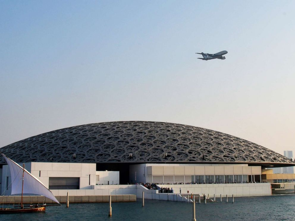 PHOTO: An Ethiad A380 flies over the Louvre Abu Dhabi Museum designed by French architect Jean Nouvel on Nov. 11, 2017, during its official opening to public on Saadiyat island in the Emirati capital.