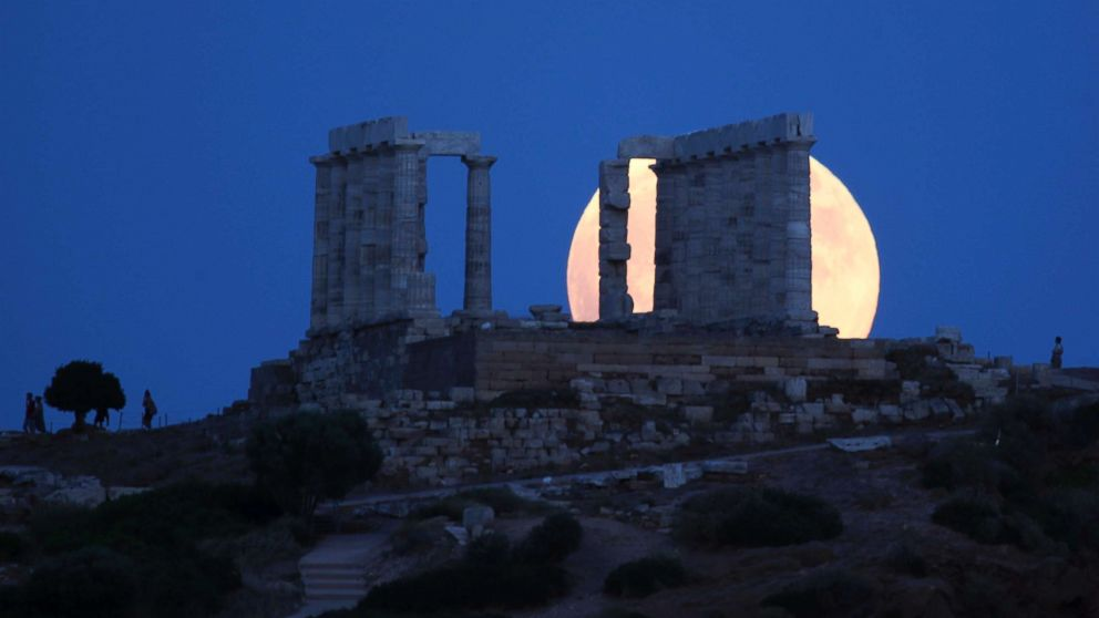 A full moon rises behind the ancient temple of Poseidon in Cape Sounio, south of Athens, July 27, 2018.