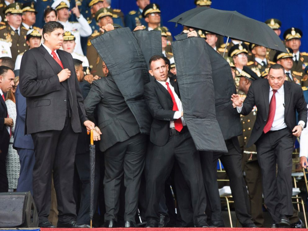In this photo released by Chinas Xinhua News Agency, security personnel surround Venezuelas President Nicolas Maduro during an incident as he was giving a speech in Caracas, Venezuela, Saturday, Aug. 4, 2018.