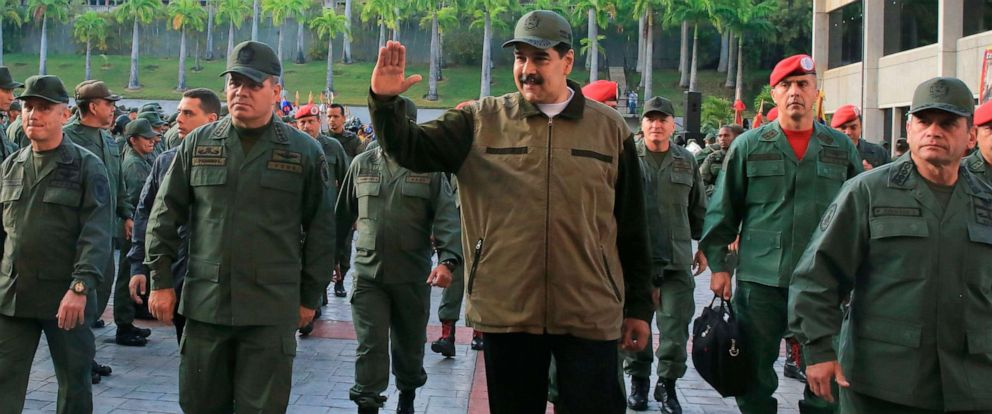 "PHOTO: Venezuelas President Nicolas Maduro, center, greets military troops accompanied by Defense Minister Vladimir Padrino, left, at the ""Fuerte Tiuna"" in Caracas, Venezuela, May 2, 2019, in a photo released by the Miraflores Palace press office."