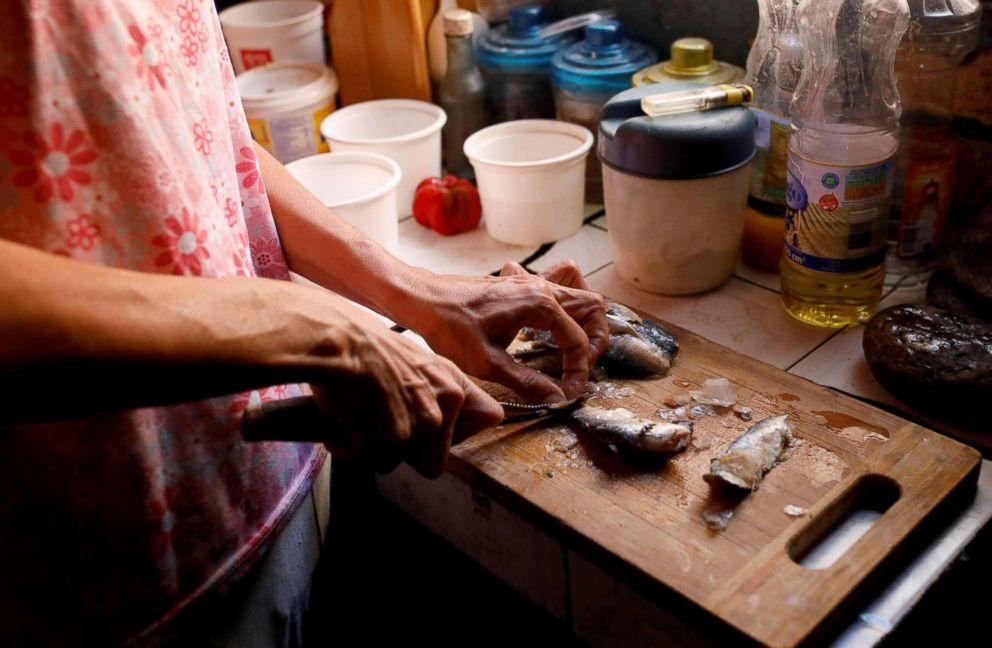 PHOTO: Yaneidi Guzman, 38, prepares sardines in her kitchen at home in Caracas, Venezuela, Feb. 17, 2019.