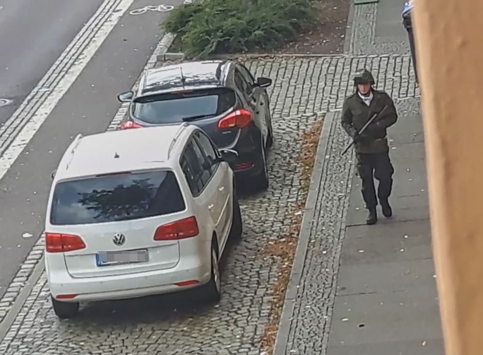 PHOTO: TOPSHOT - In this screenshot taken from a video by ATV-Studio Halle, a man walks with a gun in the streets of Halle an der Saale, eastern Germany, on Oct. 9, 2019.