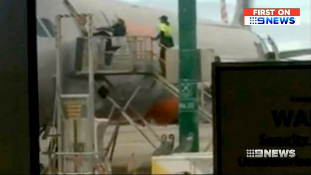 PHOTO: Framegrab from a video shows a passenger attempting to open the door to a jet and gain entry. A tarmac worker approaches him.