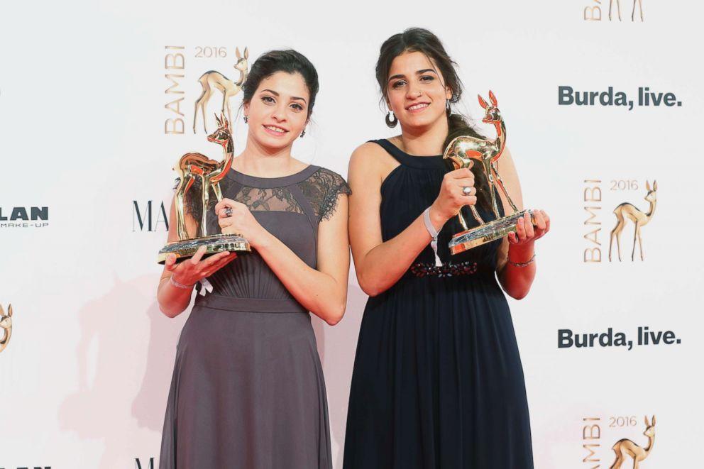 PHOTO: Yusra Mardini and Sara Mardini pose with award at the Bambi Awards 2016 winners board at Stage Theater, Nov. 17, 2016, in Berlin.