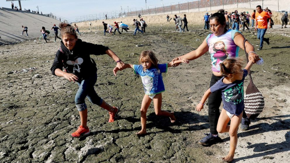 Maria Meza runs away from tear gas with her daughters Jamie Mejia Meza, aged 12 and her five-year-old twin daughters Saira Mejia Meza and Cheili Mejia Meza in front of the border wall between the U.S and Mexico, in Tijuana, Mexico Nov. 25, 2018.
