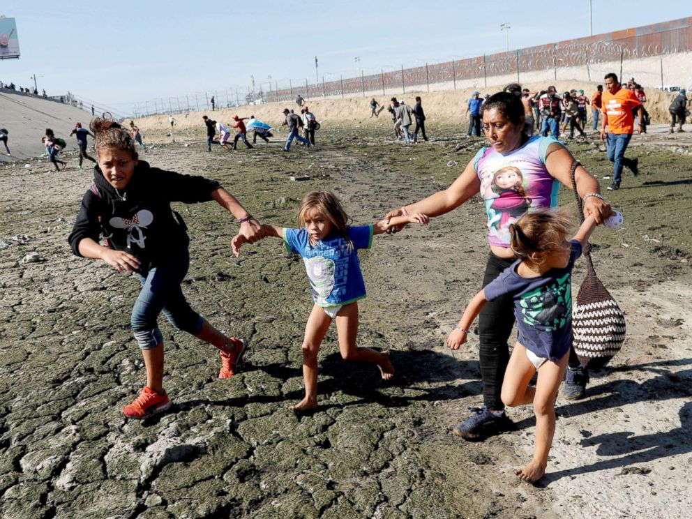 PHOTO: Maria Meza runs away from tear gas with her daughters Jamie Mejia Meza, aged 12 and her five-year-old twin daughters Saira Mejia Meza and Cheili Mejia Meza in front of the border wall between the U.S and Mexico, in Tijuana, Mexico Nov. 25, 2018.