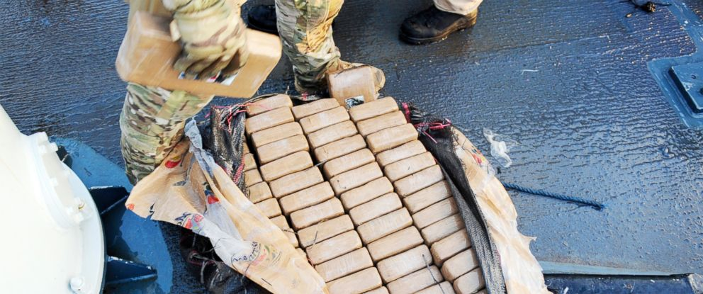 A member of the United States Coast Guard removes a 1 kg package of cocaine for testing on HMCS Whitehorse, part of the roughly 3,000 pounds of cocaine seized on April 5, 2018, during Operation CARIBBE.