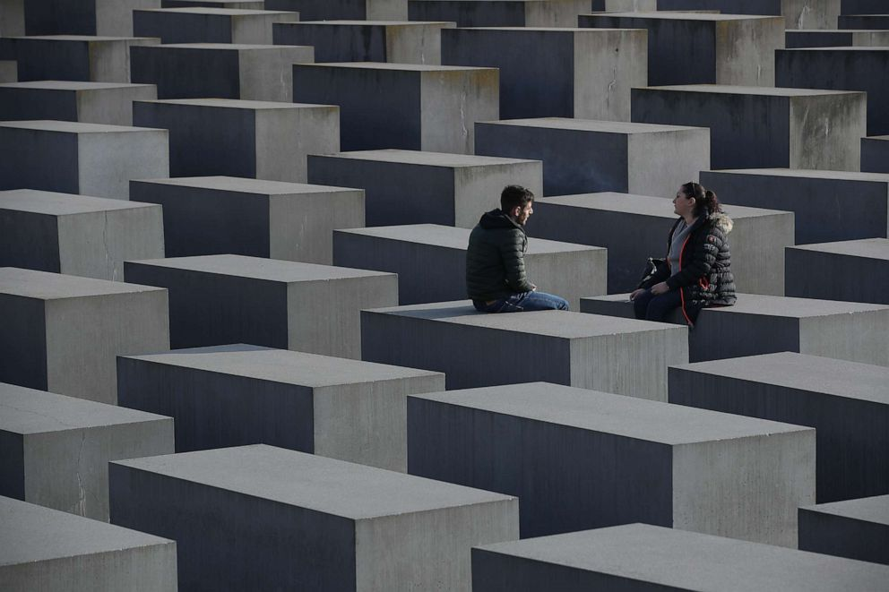 PHOTO: Two visitors sit on the Monument to the Murdered Jews of Europe, also called the Holocaust Memorial, Nov. 7, 2018, in Berlin.