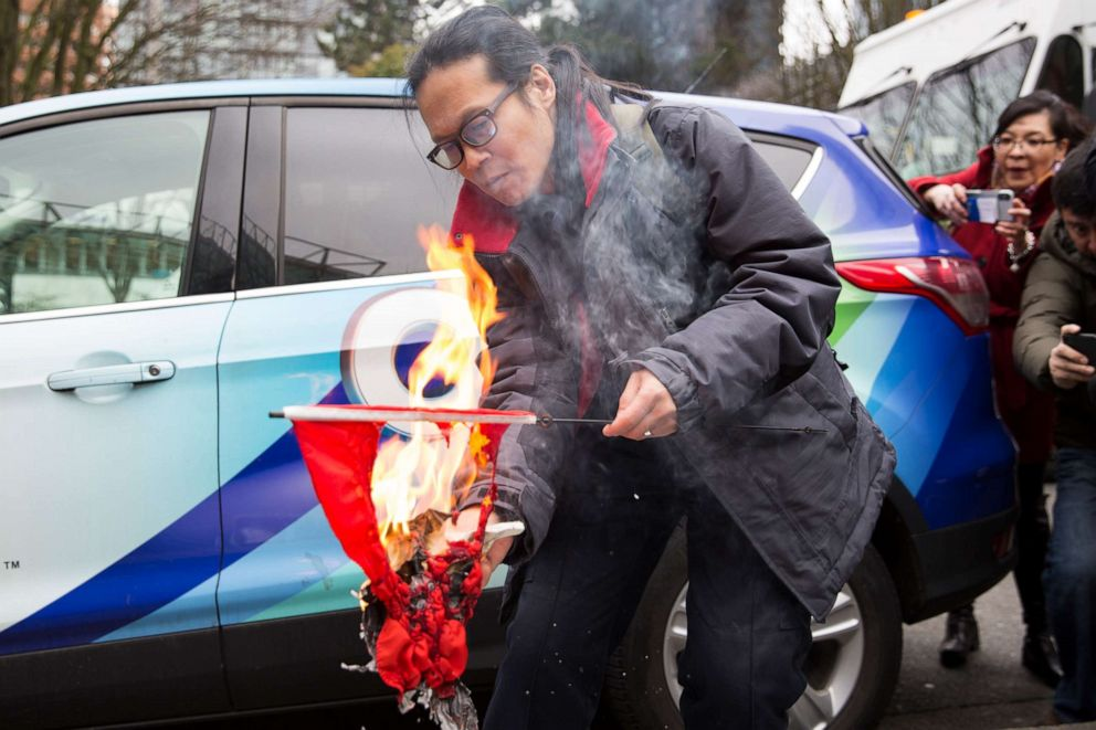 PHOTO: A man burns a Chinese flag to protest human rights abuses outside a British Columbia Supreme Court where Huawei Chief Financial Officer Meng Wanzhou appeared for an extradition hearing in Vancouver, March 6, 2019.
