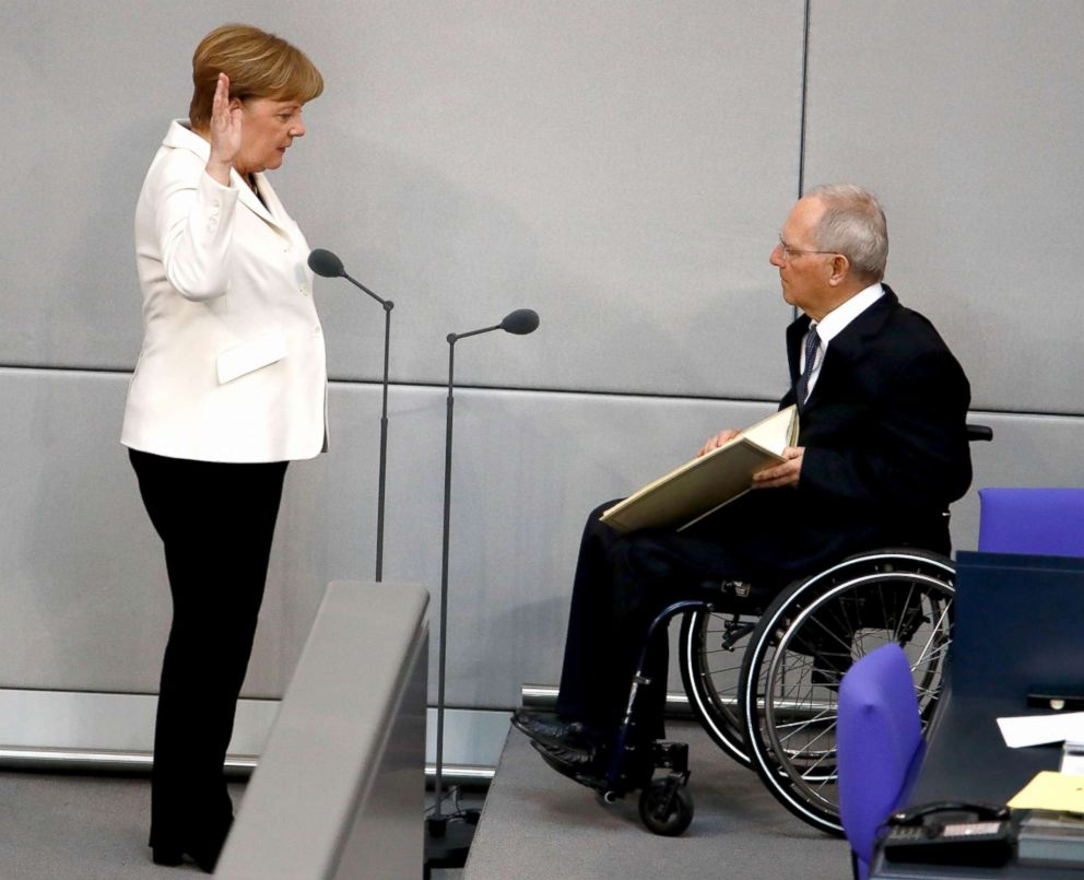PHOTO: Wolfgang Schaeuble, the president of the Bundestag administers the oath of office to German Chancellor Angela Merkel in Berlin, March 14, 2018.