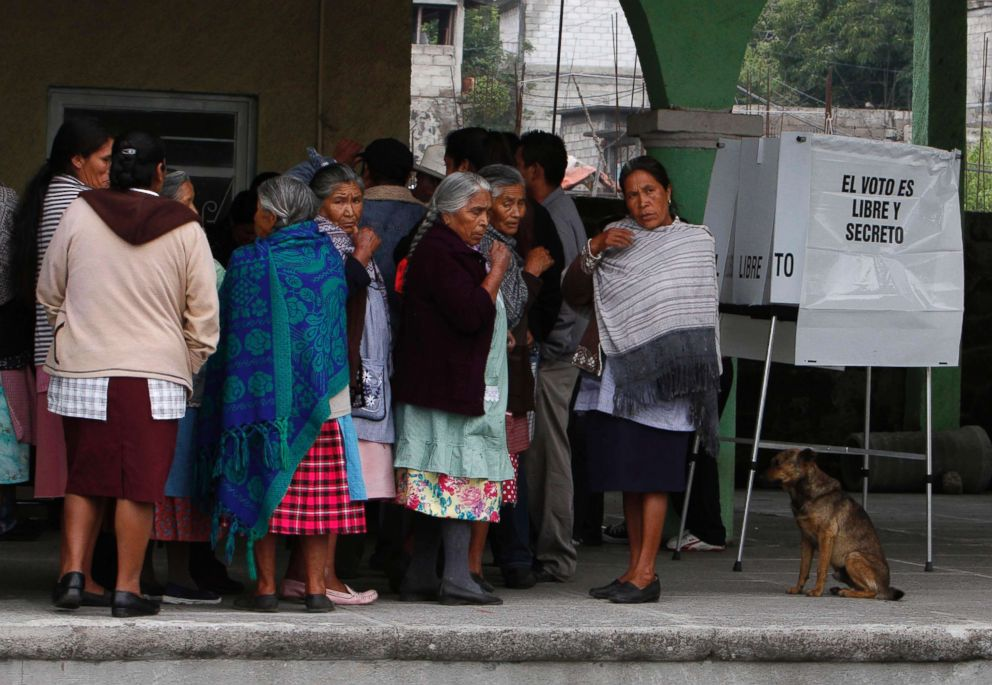 PHOTO: Residents wait in line for their turn to vote in the general election at a polling station in Santiago Xalitzintla, in the Mexican state of Puebla, July 1, 2012.