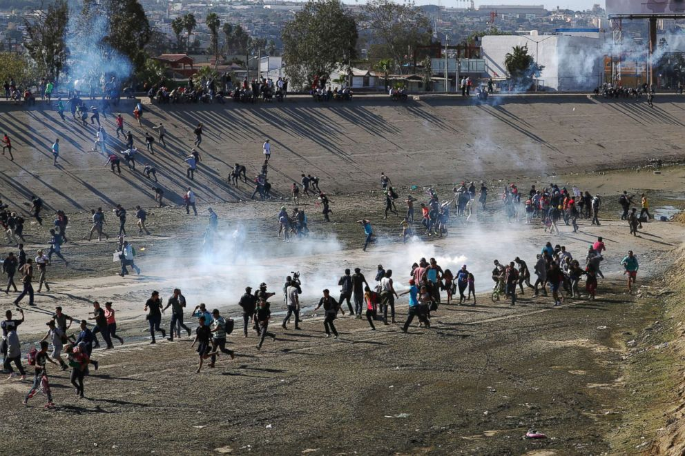 PHOTO: Migrants run from tear gas, thrown by the U.S border patrol, near the border fence between Mexico and the United States in Tijuana, Mexico, Nov. 25, 2018.