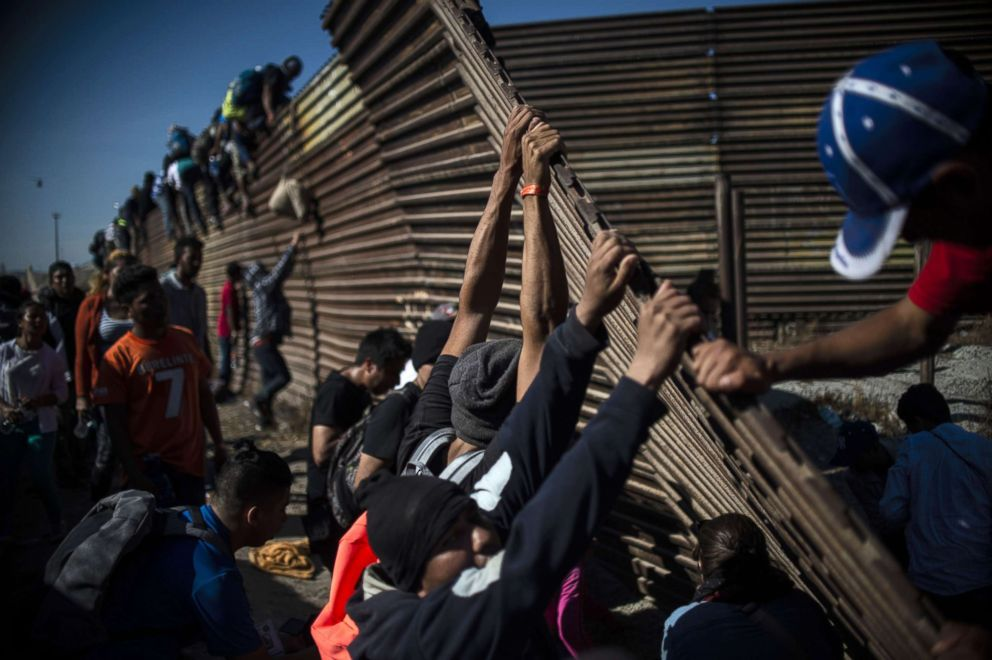 A group of Central American migrants climb the border fence between Mexico and the United States, near El Chaparral border crossing, in Tijuana, Mexico, Nov. 25, 2018.