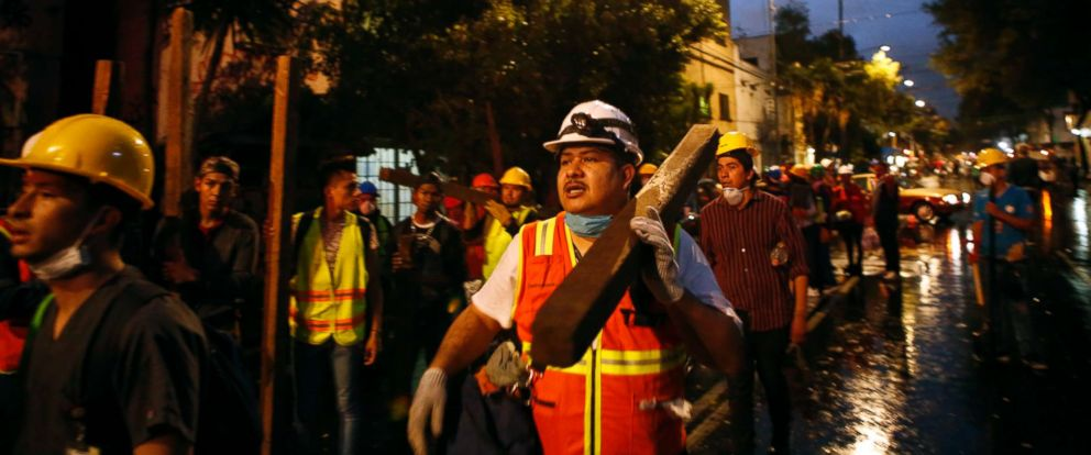 PHOTO: A group of men arrive carrying beams of wood to offer their services at a site of earthquake damage in the Roma neighborhood in Mexico City, Sept. 20, 2017.