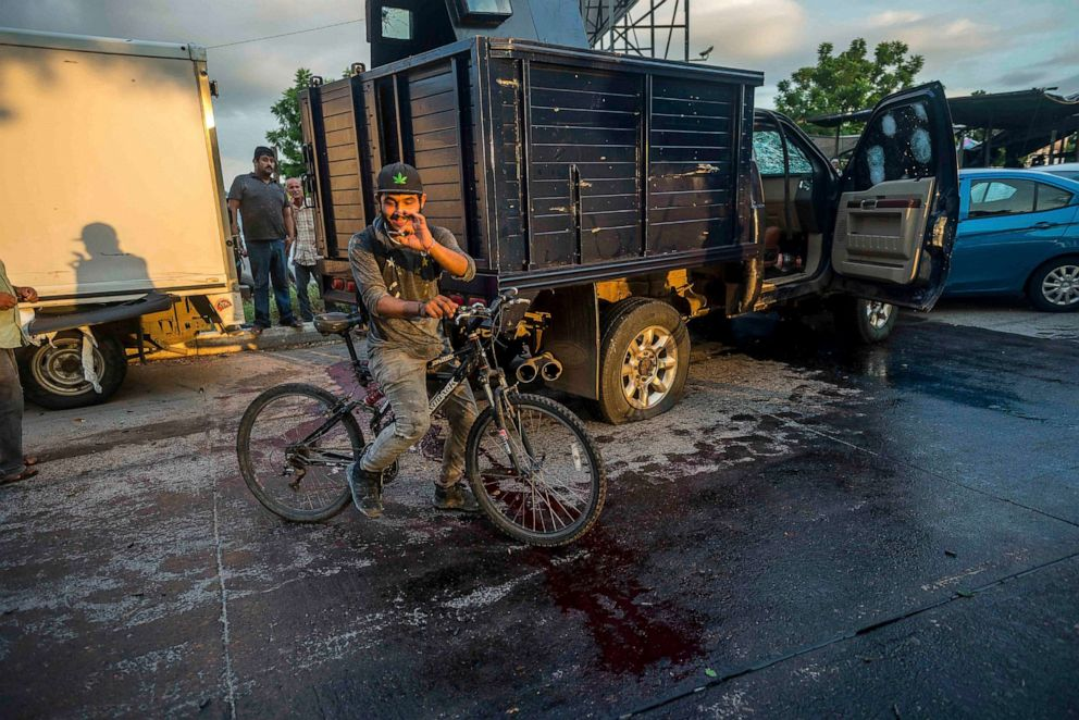 PHOTO: A man handles a bullet cartridge in a blooded street by a truck with a flat tire and covered with bullet hits after a gunfight in Culiacan, Mexico on Oct. 17, 2019.