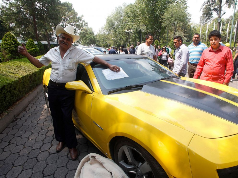 PHOTO: A man poses for photos next to a Chevrolet Camaro 2010 to be auctioned at the Los Pinos Cultural Center, once the presidential residence, in Mexico City, Sunday, May 26, 2019.