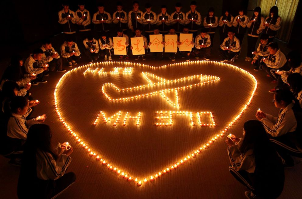PHOTO: Students at Hailiang International School lighting candles to pray for the passengers on the missing Malaysia Airlines flight MH370 in Zhuji, in Chinas Zhejiang province, March 10, 2014.