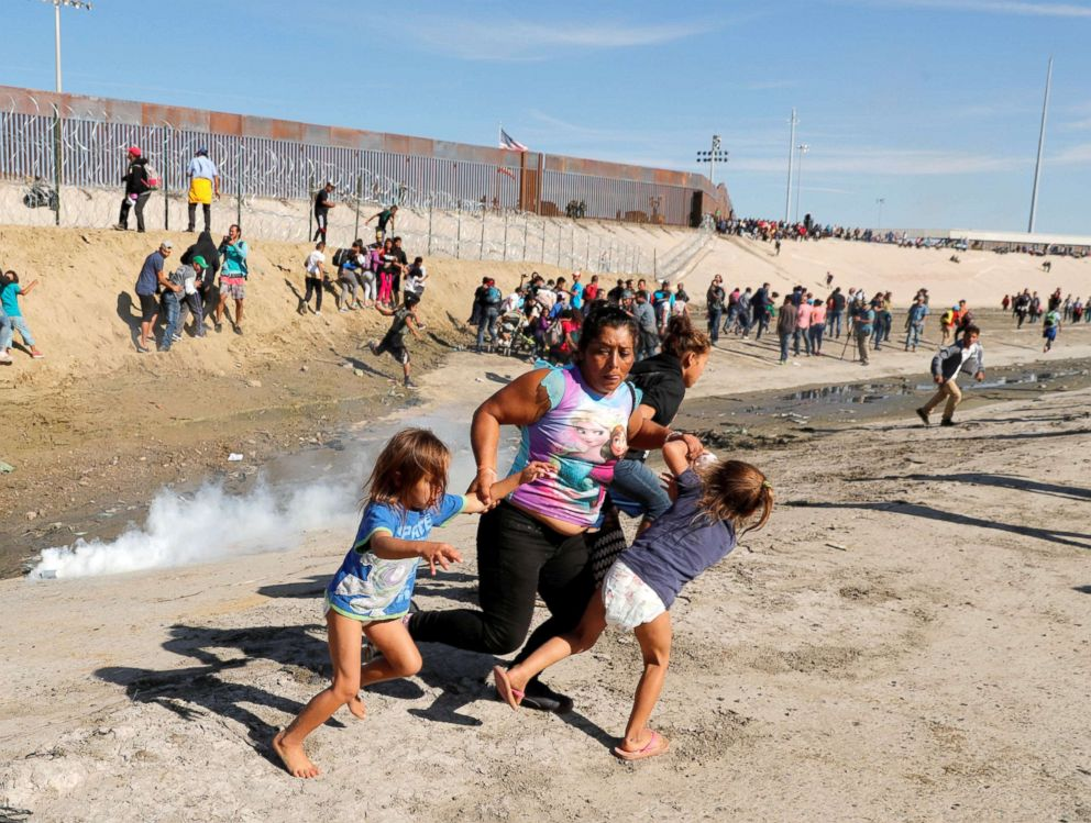 Maria Meza, center, part of a caravan of thousands from Central America trying to reach the United States, runs away from tear gas with her five-year-old twin daughters Saira Mejia Meza, left, and Cheili Mejia Meza in front of the border wall between the U.S. and Mexico, in Tijuana, Nov. 25, 2018.