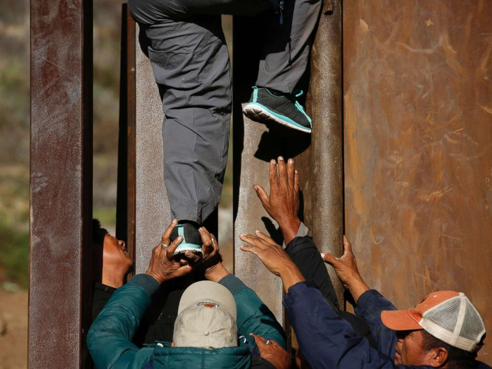 PHOTO: Honduran migrants help each other cross over the U.S. border wall to San Diego, California, from Playas in Tijuana, Mexico, Dec. 12, 2018.